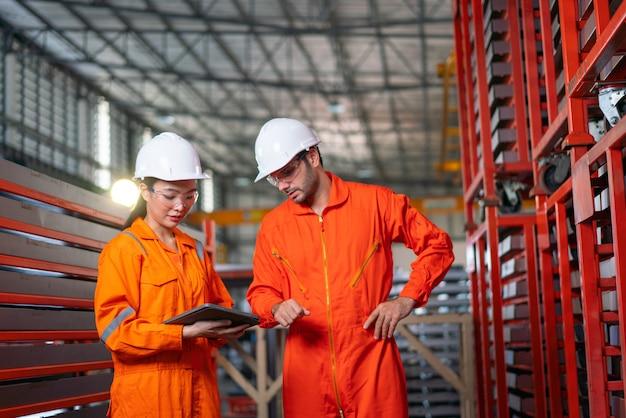 Hard hats의 남성 및 여성 산업 엔지니어는 노트북을 사용하는 동안 새로운 프로젝트에 대해 토론합니다.