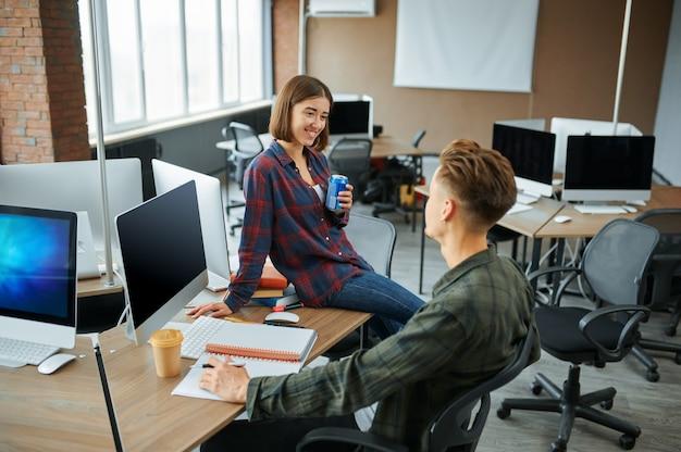 Ит-специалисты мужского и женского пола беседуют в офисе. веб-программист или дизайнер на рабочем месте, творческое занятие. современные информационные технологии, корпоративный коллектив