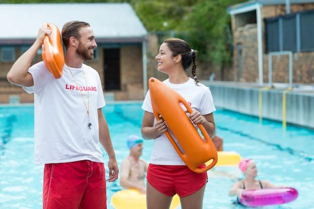 Мужские и женские спасатели, держащие спасательные баки у бассейна