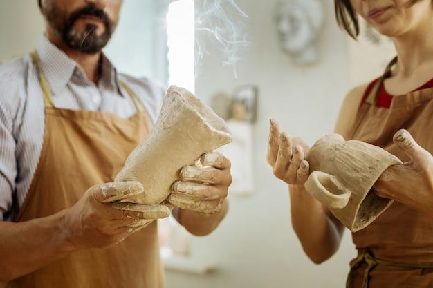Мужской и женский. профессиональные гончары мужского и женского пола вместе делают чашки и стаканы