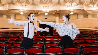 Male and female mime artist standing among chair rehearsing in auditorium