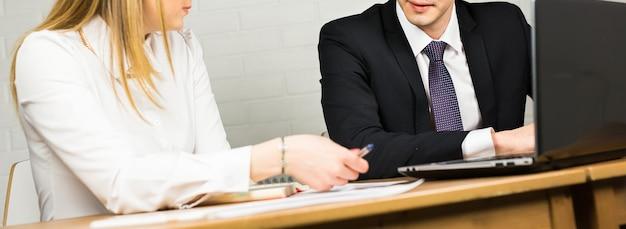 男性と女性のサラリーマン。オフィスでの会議で働いている2つの成功したビジネスパートナーの画像
