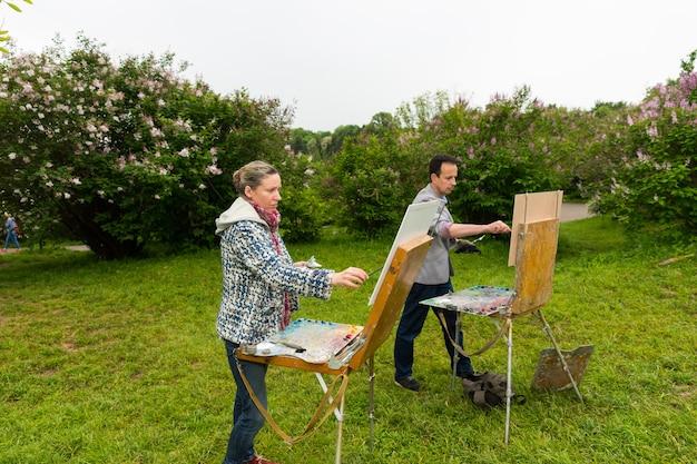 스케치북 앞에 서있는 남성과 여성의 화가는 공원에서 미술 수업을하는 동안 오일과 아크릴로 그림을 그립니다.