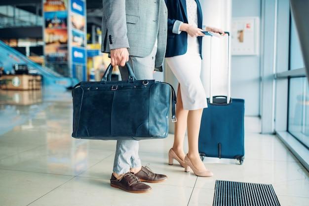 空港、出張で荷物を持つ男性と女性の乗客。ビジネスマンやエアターミナルのビジネスウーマン