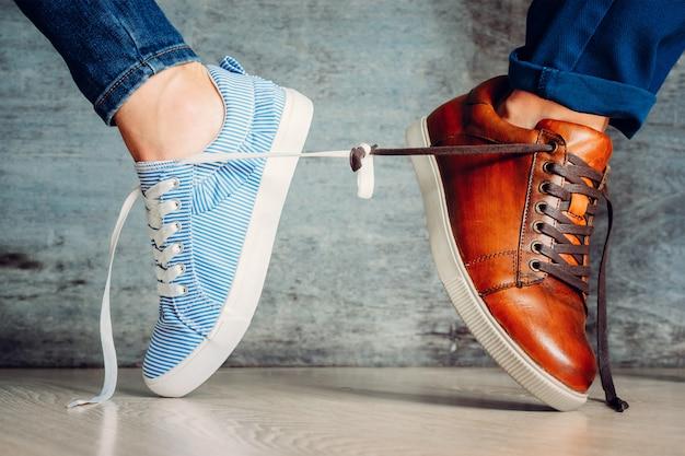 Мужские и женские туфли идут в разные стороны и перевязаны шнурками.