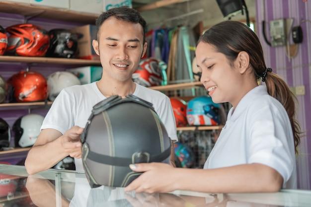 ヘルメットショップのヘルメットディスプレイラックに対してヘルメットを保持している男性と女性の店員