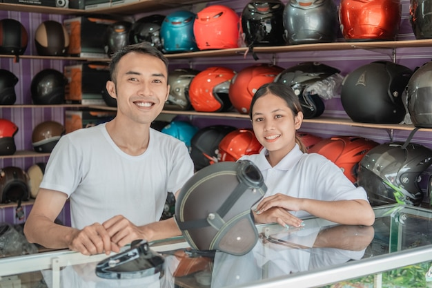ヘルメットショップのヘルメット陳列棚の近くに立っている男女の店員