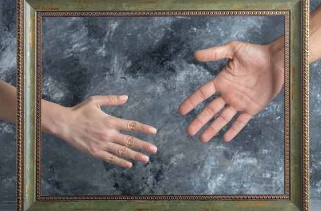 額縁の真ん中に手を示す男性と女性。