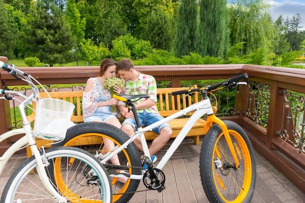 벤치에 앉아 있는 남성과 여성은 자전거를 맞은편에 주차하고 공원에서 꽃 냄새를 맡는다