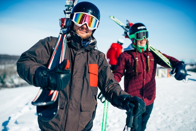 男性と女性のスキーヤーは、スキーとポールを手に、青い空と雪に覆われた山でポーズします。冬のアクティブなスポーツ、極端なライフスタイル。ダウンヒルスキー