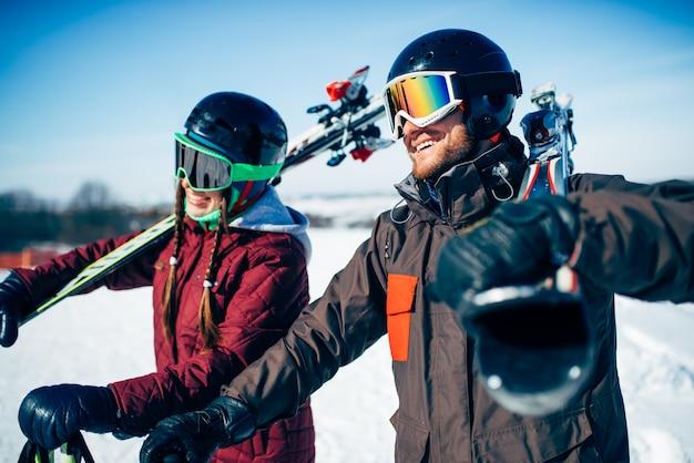 男性と女性のスキーヤーがスキーとポールでポーズします。