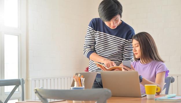 남학생과 여학생이 스마트 폰과 노트북으로 선생님에게 작업을 보내는 프로젝트를 논의하고 있습니다.