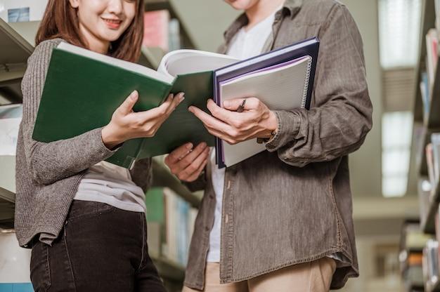 대학 도서관에서 시험을 위해 책을 읽는 남학생과 여학생. 교육, 학교, 도서관 및 지식 개념입니다.