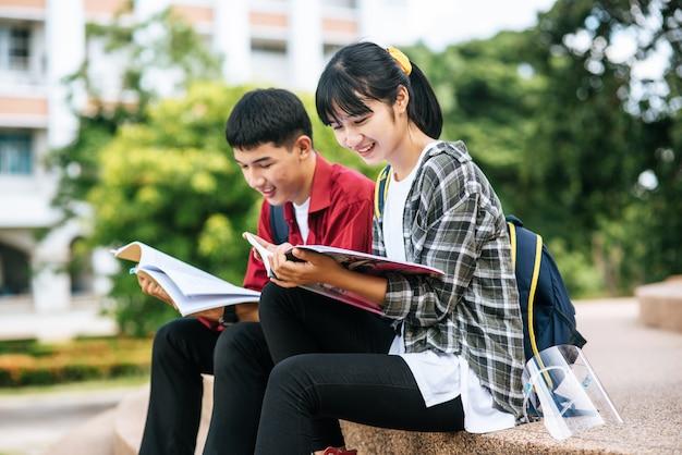 앉아서 계단에서 책을 읽고 남녀 학생.