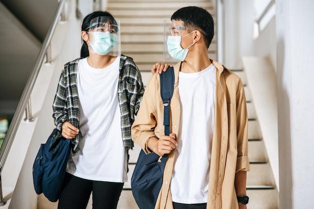 남녀 학생은 건강 마스크를 쓰고 계단에서 서로 대화합니다.