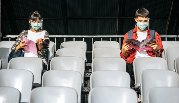 남녀 학생은 마스크를 쓰고 필드 의자에 앉아서 읽습니다.
