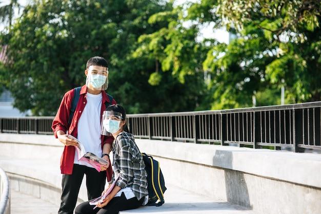 마스크를 착용하는 남녀 학생이 앉아서 계단에서 책을 읽습니다.