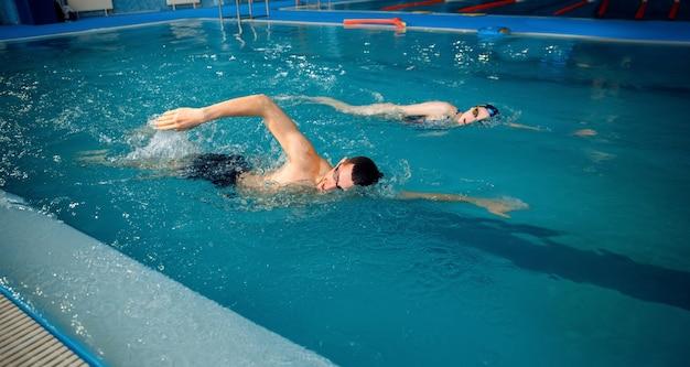 男性と女性のスイマーはプールで泳ぐ