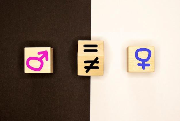 Мужские и женские символы нарисованы на деревянных блоках на черно-белом фоне. равенство.
