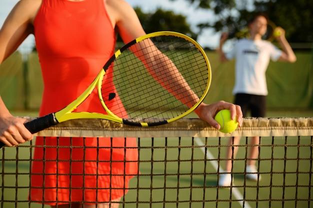 ラケットを持った男性と女性のテニス選手、屋外コートでのトレーニング。アクティブで健康的なライフスタイル、人々はスポーツゲーム、ラケットでのフィットネストレーニングをプレイします