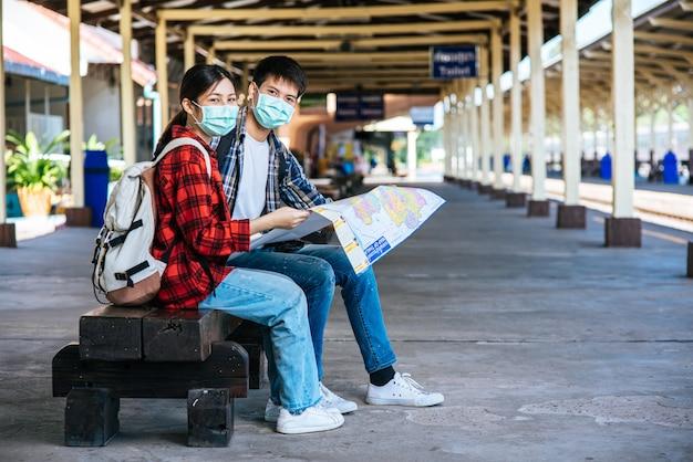 男性と女性の観光客が鉄道の横にある地図を見てください。