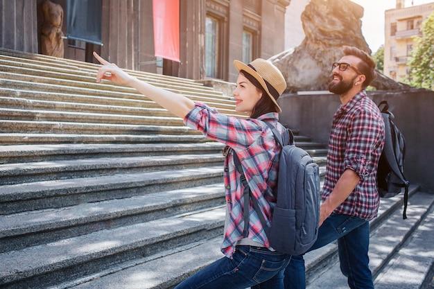 Мужские и женские туристы поднимаются по ступеням. она указывает вперед. они держат друг друга за руки и на спине рюкзаки. люди выглядят хорошо и позитивно.