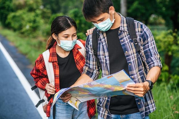 Туристы мужского и женского пола носят медицинские маски и смотрят на карту на улице.