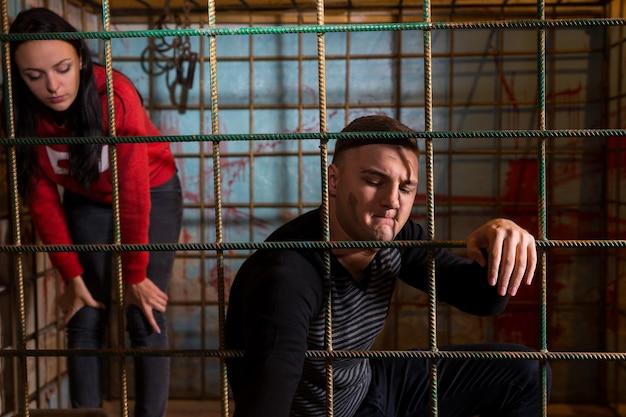 Жертвы мужского и женского пола, заключенные в металлическую клетку с забрызганной кровью стеной позади них, пытаются выбраться.