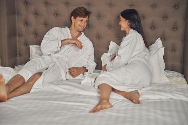 침실에서 함께 시간을 보내는 흰색 부드러운 목욕 가운을 입고 남성과 여성
