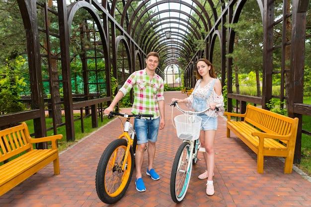 공원의 아치 밑의 통로에서 자유 시간을 보내는 현대적인 자전거를 탄 남성과 여성