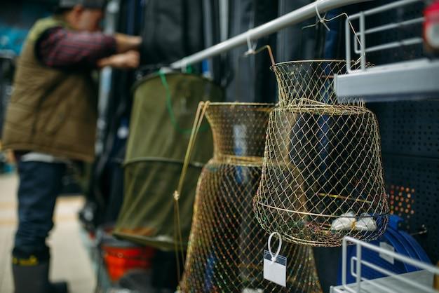 Рыболов мужского пола, выбирая сеть в рыболовном магазине, крючки и фенечки