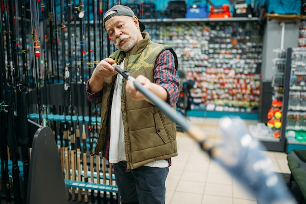 Рыболов мужского пола, выбирая удочку в магазине рыбной ловли