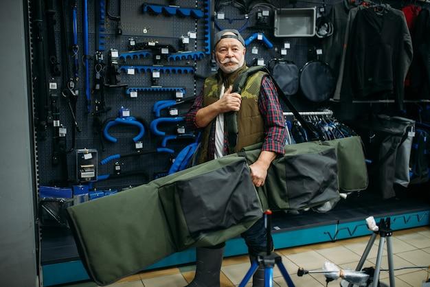 Рыболов-мужчина держит в рыболовном магазине большой чемодан для удочек.