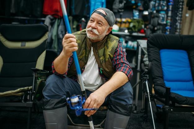 Рыболов мужского пола в резиновых сапогах держит удочку в магазине рыбной ловли