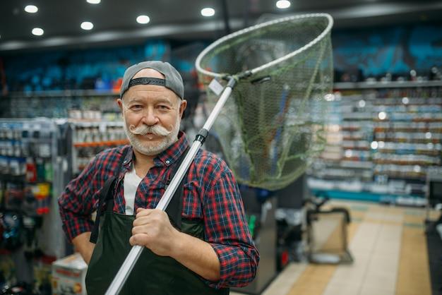 Рыболов-мужчина в резиновом комбинезоне держит сеть в рыболовном магазине, крючки и фенечки