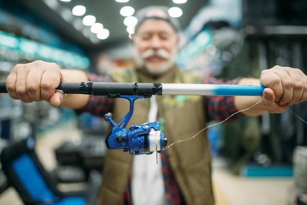 Рыболов мужского пола показывает удочку с катушкой в рыболовном магазине.