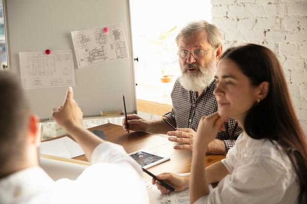 Архитектор-инженер-мужчина представляет проект будущего дома для молодой семьи. человек, работающий в офисе с документами, планом. первый дом, промышленное здание, концепция. переезд на новое место жительства.
