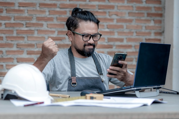 Male architect or engineer working at home drawing the construction project bile phone on the working desk