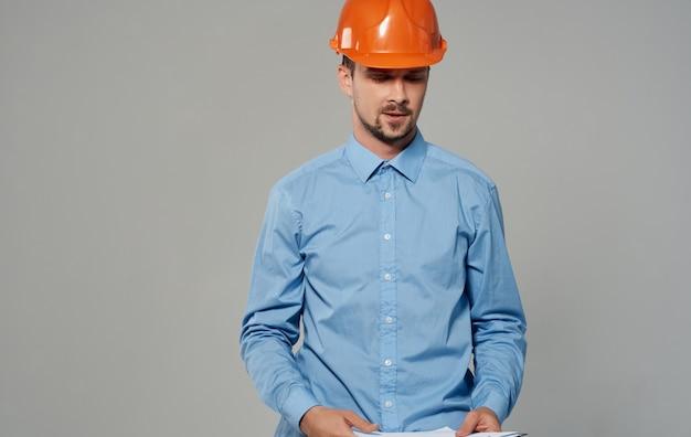 오렌지 하드 모자 작업 회색 벽에 남성 건축가 자른보기.
