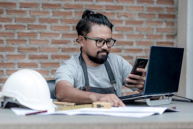 建設プロジェクトを描く自宅で働く男性の建築家またはエンジニア、作業机の上で携帯電話を使用してラップトップで作業する建築家。ビジネスとテクノロジーの概念。