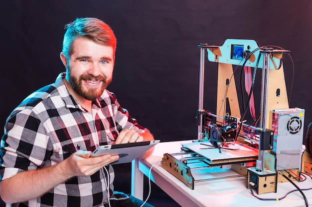 Мужской архитектор с помощью 3d-принтера в офисе.
