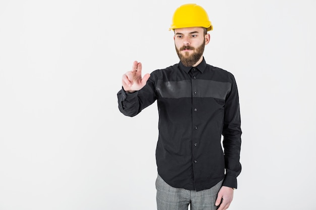 Male architect wearing yellow hardhat gesturing