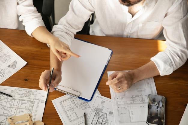 Инженер-мужчина представляет проект будущего дома для молодой семьи.