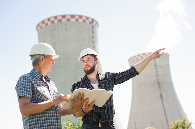 Male architects reviewing documents together at electric power plant.