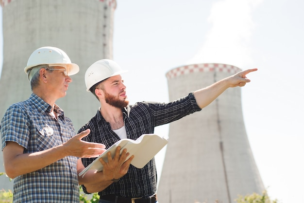 Male architects reviewing documents together at electric power