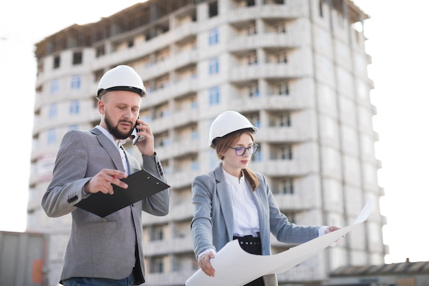 Male architecture talking on cellphone standing near female architecture holding blueprint at construction site