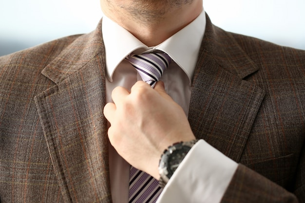 Male arm in brown suit set tie closeup