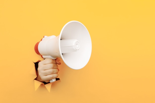 Male arm hold megaphone isolated through torn yellow paper.
