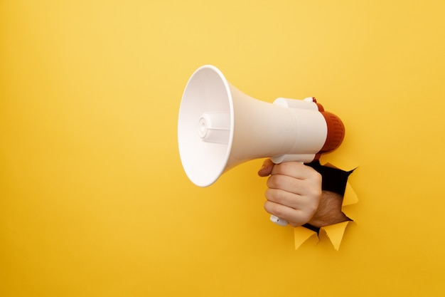 Male arm holding megaphone isolated through torn yellow background.