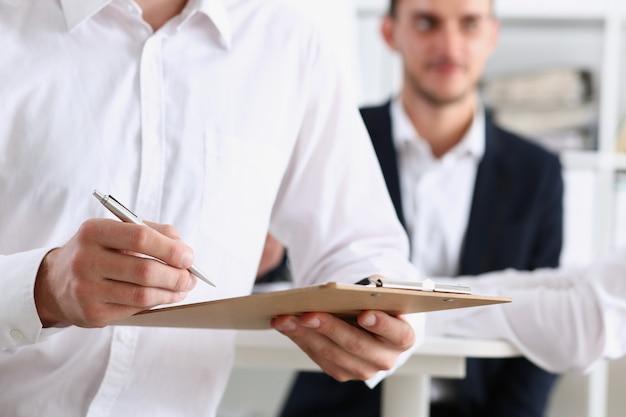 Мужская рука в рубашке держит серебряную ручку и блокнот
